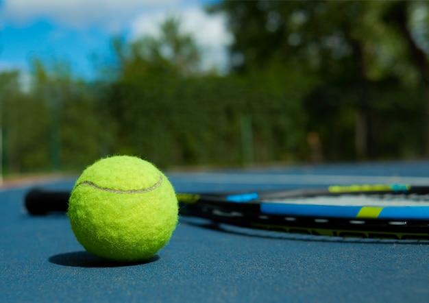 Feche acima da bola de tênis no tapete profissional da raquete, colocando no tapete azul do campo de tênis.