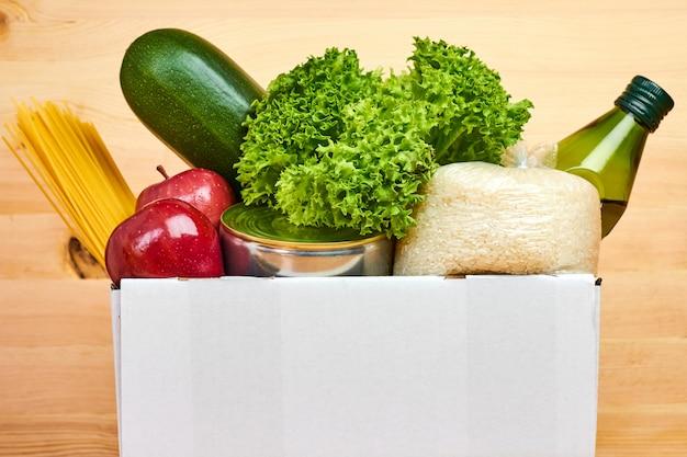 Feche acima da caixa branca com diferentes produtos saudáveis em uma parede de madeira. serviço de entrega de comida de supermercado ou loja online