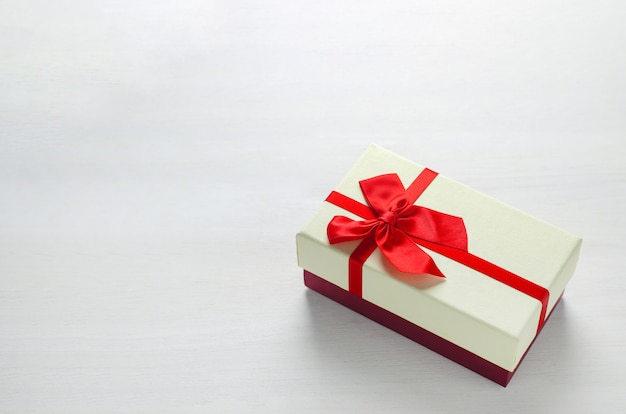Feche acima da caixa de presente de dois tons com fita vermelha