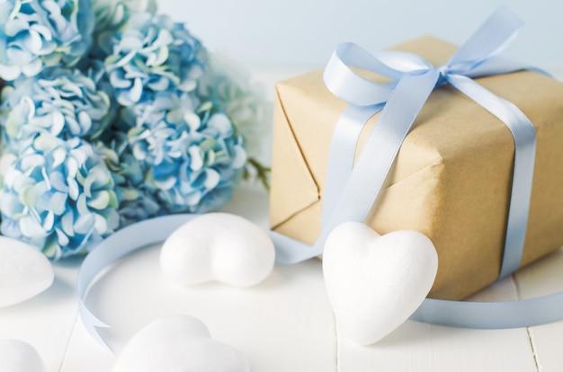 Feche acima da caixa de presente de reciclagem marrom com coração branco e flores de hortênsia azul