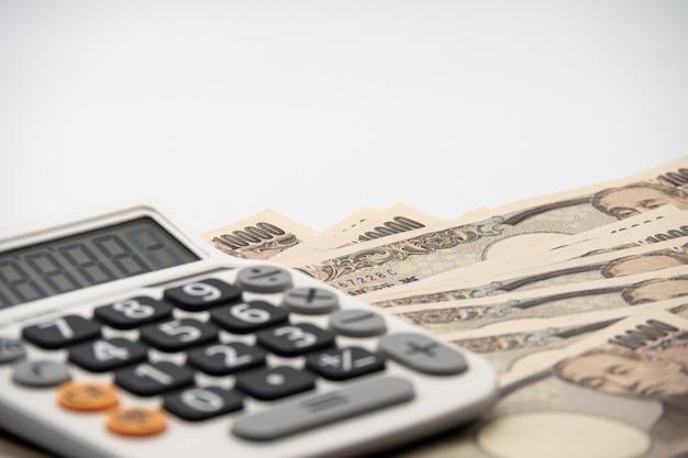 Feche acima da calculadora na cédula japonesa do dinheiro dos ienes da moeda. economia do japão.