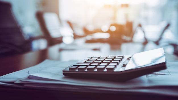 Feche acima da calculadora na mesa de trabalho do negócio, fundo escuro.