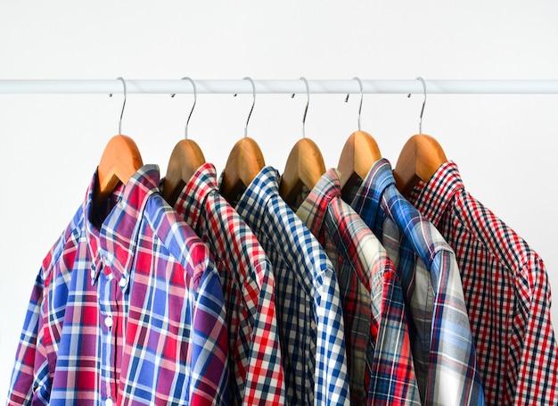 Feche acima da camisa quadriculada vermelha e azul de manga longa em cabide de madeira sobre branco