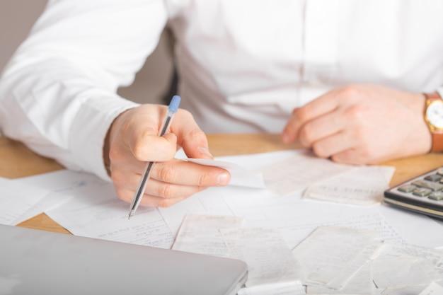 Feche acima da caneta de exploração de mão de empresário ou contador trabalhando no documento de contabilidade calculadora e laptop no escritório, conceito do negócio