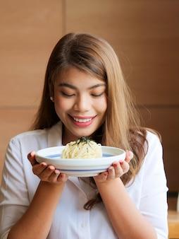 Feche acima da cara asiática feliz da mulher que guarda o macarronete nas mãos no restaurante, conceito do tempo de almoço.