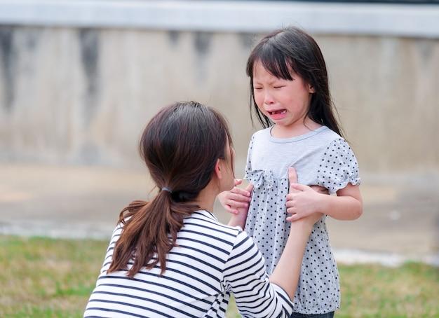 Feche acima da cara da menina que grita em seus braços da mãe.