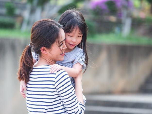 Feche acima da cara feliz da menina em seus braços da mãe.