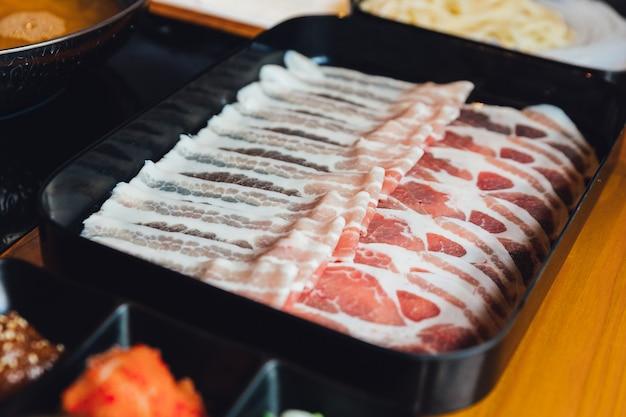 Feche acima da carne de porco rara de kurobuta das fatias do prêmio com textura alto-marmoreada.