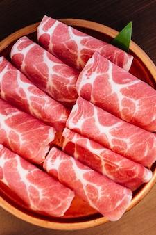 Feche acima da carne de porco rara superior de kurobuta das fatias (porco preto) com textura baixo-marmoreada.
