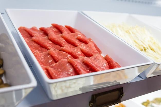 Feche acima da carne dentro da linha dos alimentos frescos para o bufete do sukiyaki no refrigerador.