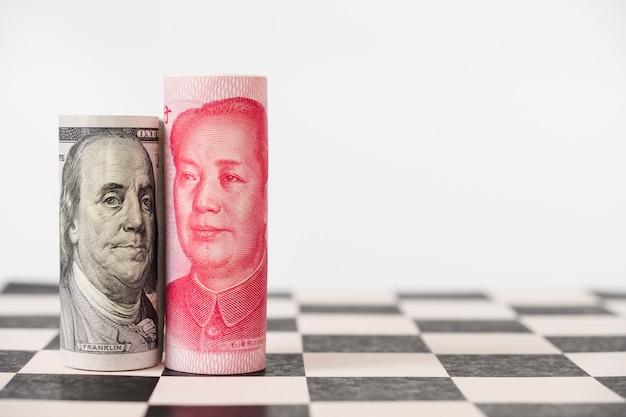 Feche acima da cédula do dólar americano e da cédula de yuan no tabuleiro de xadrez com fundo branco.