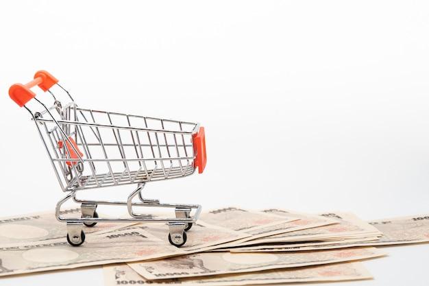 Feche acima da cédula japonesa do dinheiro dos ienes da moeda no carrinho de compras pequeno. economia do japão e mercado online.