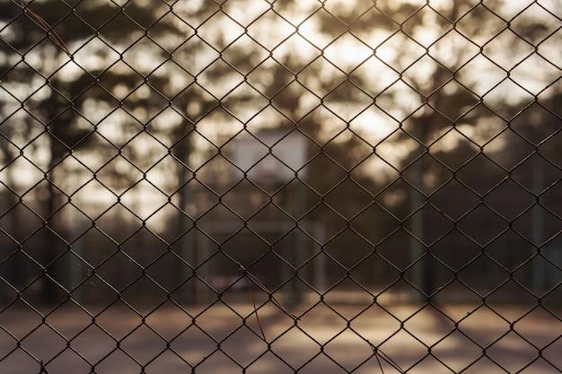 Feche acima da cerca da ligação no campo de basquete