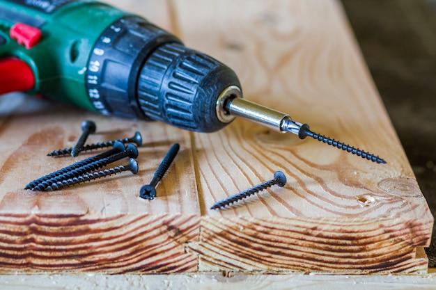 Feche acima da chave de fenda elétrica com alguns parafusos que colocam na tabela de madeira áspera velha ou em pranchas naturais do vintage. construção, reparação e conceito de manutenção em casa
