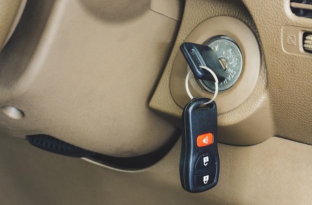 Feche acima da chave do carro com controle remoto no buraco da fechadura
