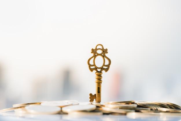 Feche acima da chave na pilha da moeda com arquitectura da cidade como fundos.