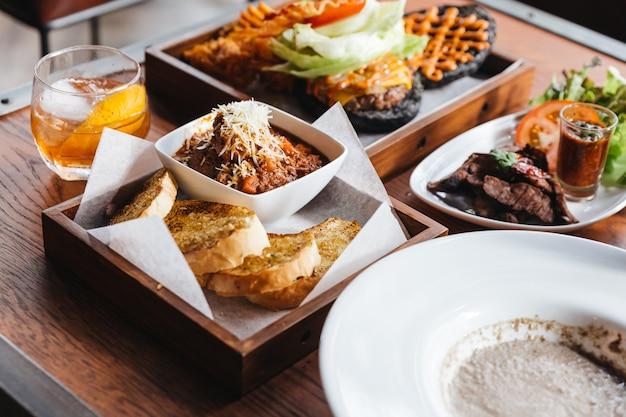 Feche acima da cobertura do molho da carne com mozzarella, servido com pão de alho na tabela de madeira com cheeseburger do carvão vegetal, carne de porco grelhada e cocktail.