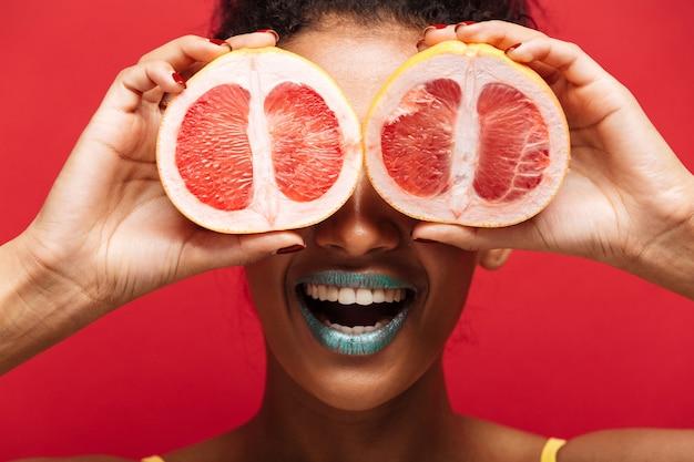 Feche acima da comida sorrindo mulher afro-americana se divertindo cobrindo os olhos com duas metades de laranja madura fresca, isolada sobre parede vermelha
