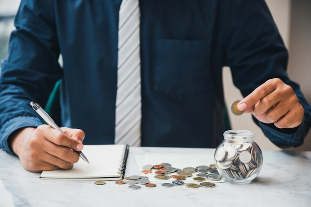 Feche acima da contabilidade do homem de negócios que guarda moedas que põem no vidro