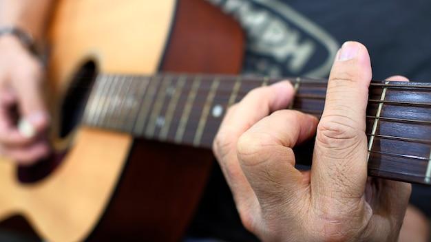 Feche acima da corda da imprensa do dedo no clássico de madeira da guitarra.