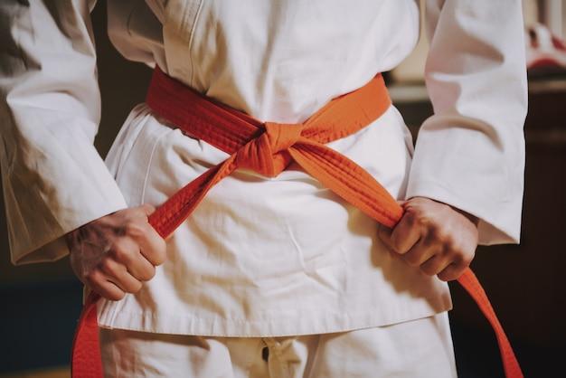 Feche acima da correia vermelha no keikogi branco do lutador das artes marciais.