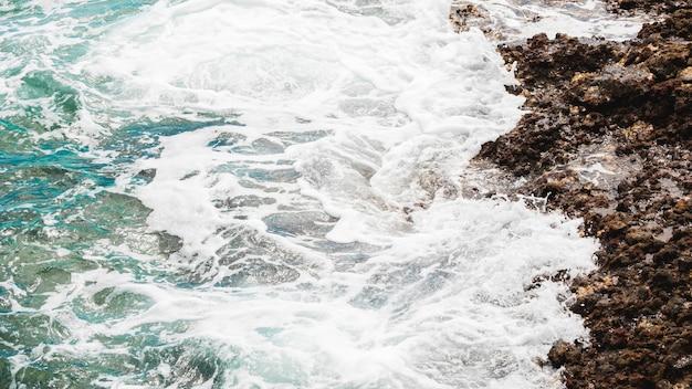 Feche acima da costa rochosa com água cristalina
