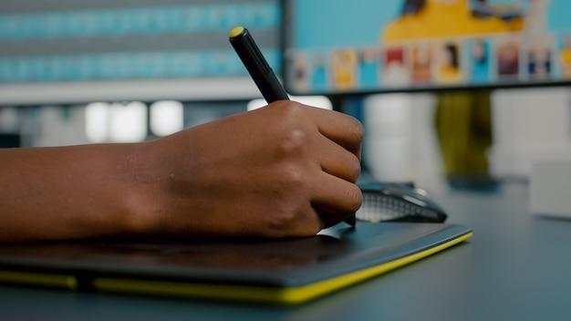 Feche acima da edição do designer de fotos com o ilustrador de tablet e lápis, desenhando no tablet gráfico han ...
