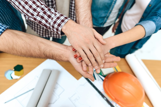 Feche acima da equipe de arquitetos designers de mãos dadas.