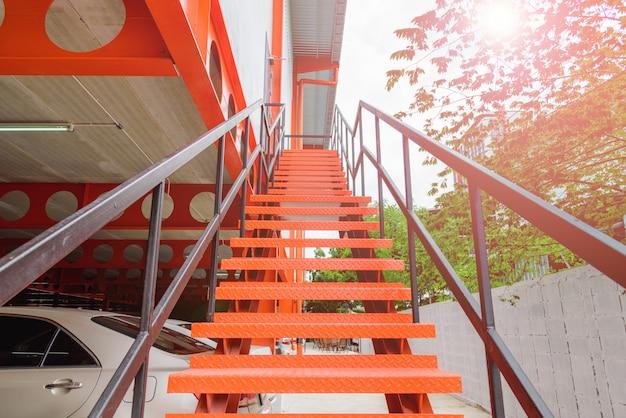 Feche acima da escadaria ou da escadaria de aço alaranjada fora do edifício.