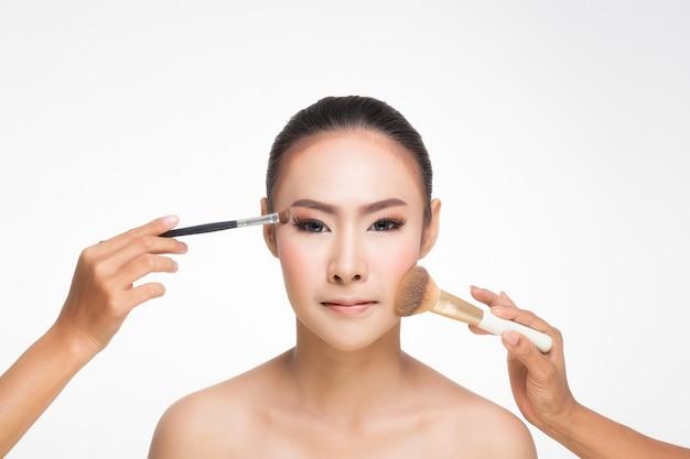 Feche acima da escova da face e da composição da rapariga.
