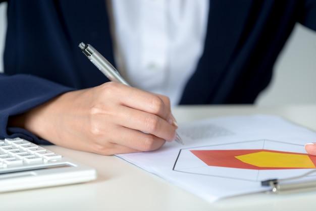 Feche acima da escrita da mão da mulher de negócios e da análise nos gráficos de negócio