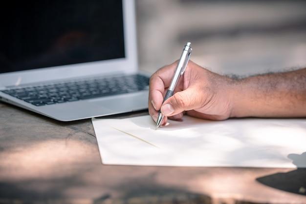 Feche acima da escrita da mão do homem algo no caderno na tabela de madeira com o laptop ao lado dele.