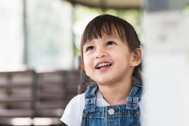 Feche acima da face de asiático pequeno adorável com sorriso grande.