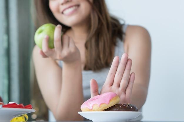 Feche acima da fêmea que usa a mão escolha a maçã verde.