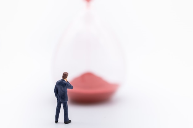 Feche acima da figura diminuta do homem de negócios que está com sandglass vermelhos no branco.