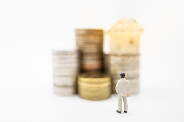 Feche acima da figura diminuta do homem de negócios que está e que olha à pilha de moedas e do mini brinquedo da casa na parte superior.