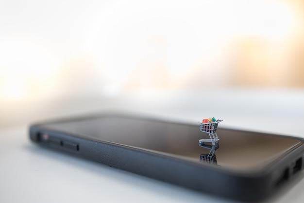 Feche acima da figura miniagure do carrinho de compras / trole no telefone móvel esperto com espaço da cópia.
