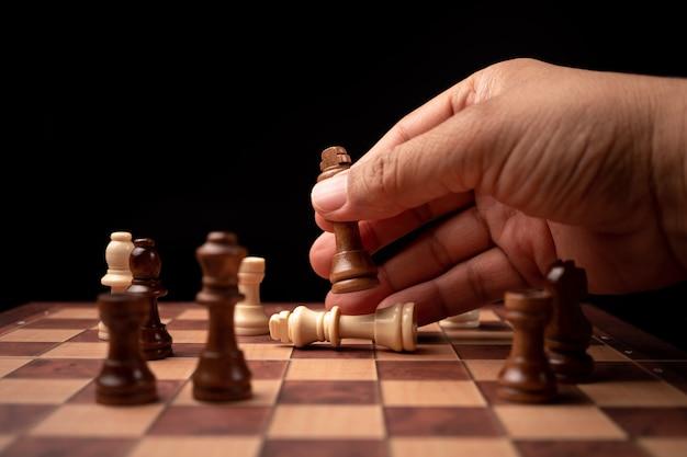 Feche acima da figura movente da xadrez do homem de negócios seguro das mãos no jogo do sucesso da competição.