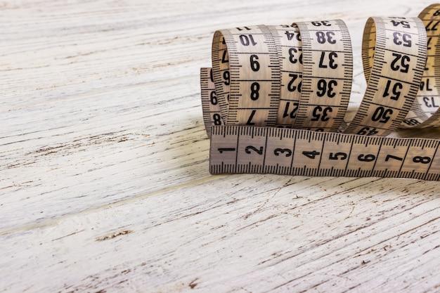 Feche acima da fita de medição do alfaiate no fundo de madeira da tabela. fita de medição branca dept superficial de campo