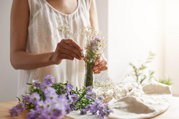 Feche acima da florista fêmea nova que faz o ramalhete macio no local de trabalho. copie o espaço.