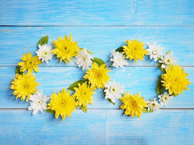 Feche acima da forma branca e amarela da infinidade das flores do crisântemo na madeira azul.