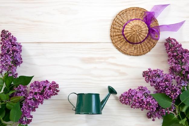 Feche acima da foto com a lata molhando do brinquedo, pouco chapéu de palha e lilás no fundo de madeira branco.