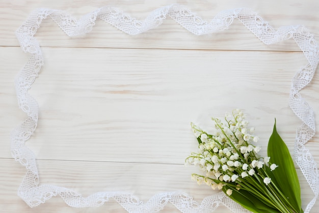 Feche acima da foto com o ramalhete dos lírios do vale no fundo de madeira branco