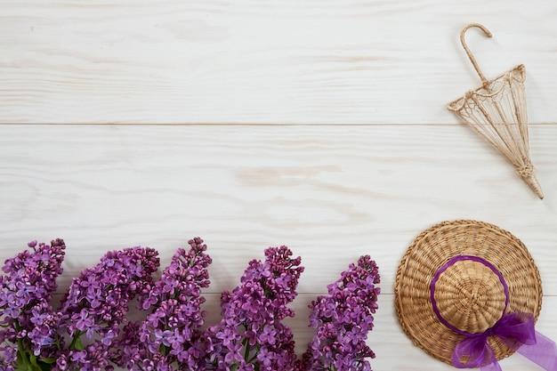 Feche acima da foto com pouco chapéu de palha, guarda-chuva decorativo e ramos lilás