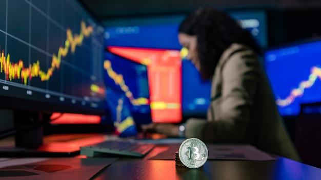 Feche acima da foto da criptomoeda bitcoin na frente do tipo de investidor comerciante corretor asiático feminino no relatório de gráfico gráfico de estudo de computador portátil quando fizer transações on-line no fundo desfocado.
