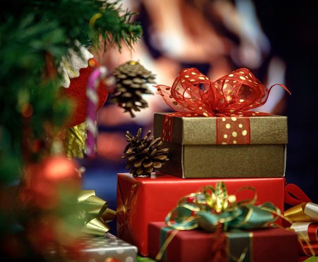 Feche acima da foto da pilha de caixas de presente embrulhado de véspera de natal com fita vermelha verde e dourada com decoração pinheiro de natal com esferas brilhantes bolas sinos meias flocos de gelo com pouca luz.
