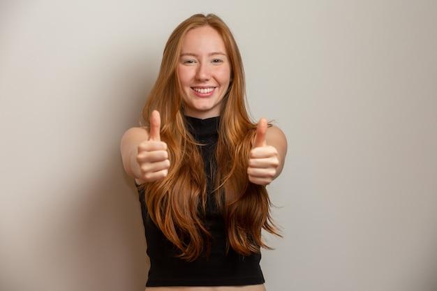 Feche acima da foto da senhora consideravelmente foxy que levanta o polegar que expressa acima a camisa ocasional quadriculado do desgaste do acordo camisa isolada. ruiva. ok.