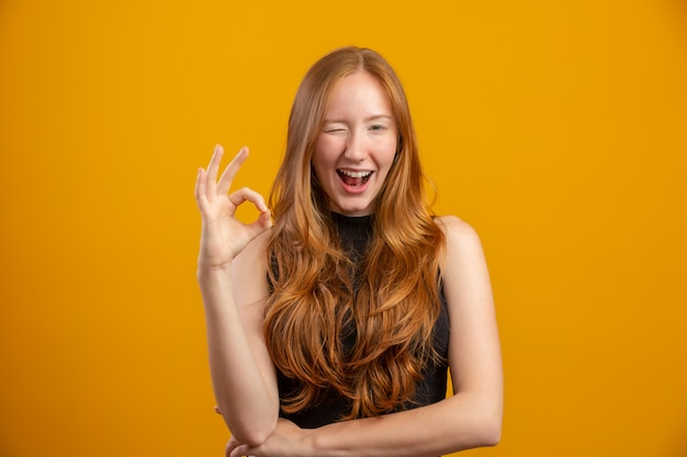 Feche acima da foto da senhora foxy bonita que levanta o olho piscando aprovado que expressa o acordo vista a camisa ocasional quadriculado isolada parede amarela da cor. ruiva. ok.