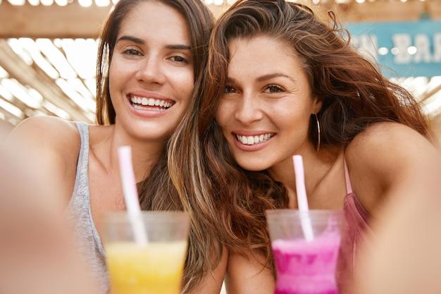Feche acima da foto de mulheres europeias bonitas se divertir, comemorar algo, beber coquetéis de verão, fazer selfie, compartilhar fotos em redes sociais.