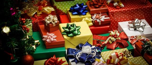 Feche acima da foto de um monte de pilha de caixas de presente embrulhado de véspera de natal feliz com fitas coloridas e arcos com decoração pinheiro de natal com esferas brilhantes bolas sinos meias flocos de gelo nas proximidades.